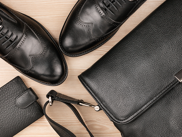 Classic black shoes, briefcase and purse on the wooden floor
